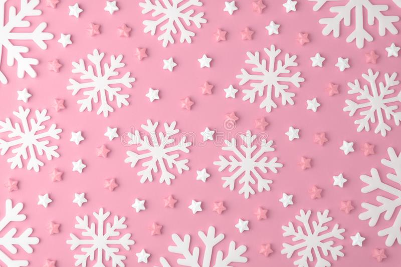 Christmas snowflake pattern with Lollipops and sweets Candy flat lay on pink pastel background. Minimal concept stock photo