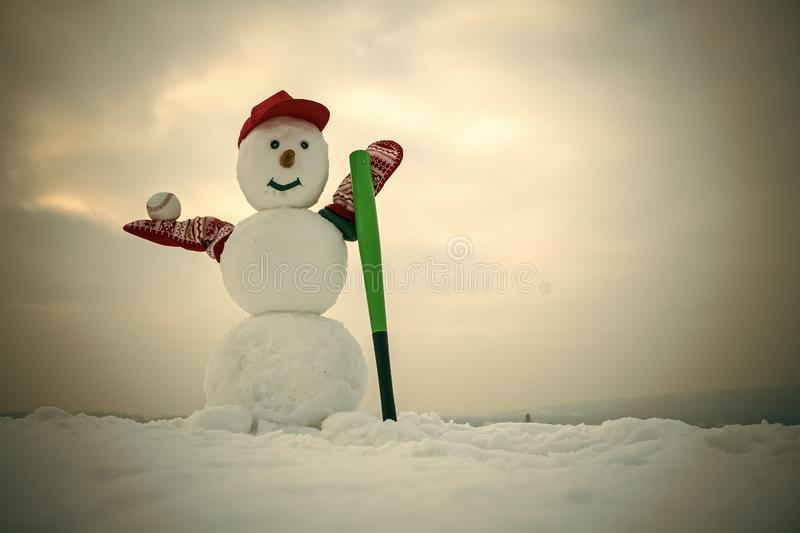 Christmas snowman in cap with baseball bat in winter stock image