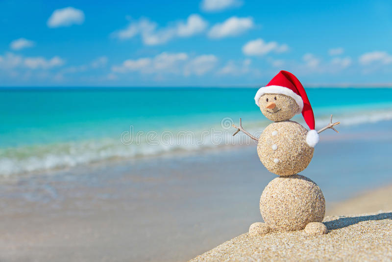 Christmas snowman in santa hat at tropical ocean beach stock photography