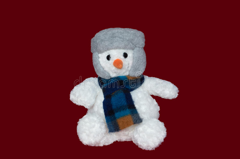 Christmas - Snowman wearing a Hat and Scarf. A soft plush snowman wearing a grey hat and check scarf. Isolated on a red background stock photo