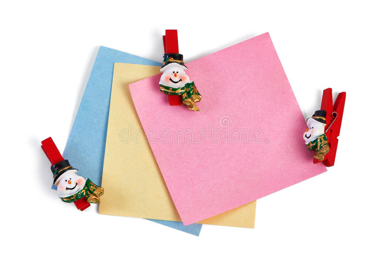 Christmas snowmans clothespins holding note paper isolated. Christmas snowmans clothespins holding note paper on white background stock photography