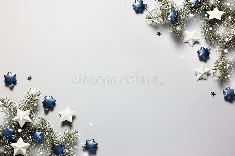 Christmas snowy border of shiny balls and classic blue stars, evergreen branches on neutral pastel grey background stock photography