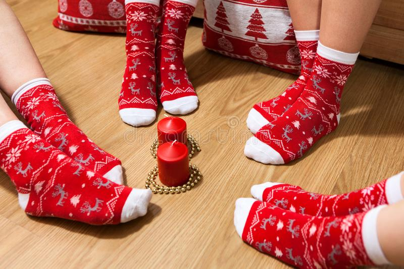 Christmas socks on feet of family. Adults and children legs placed on floor around red candles. Christmas socks on feet of family. Adults and children legs royalty free stock image
