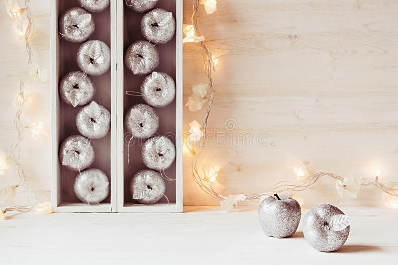 Christmas soft home decor of silver apples and lights burning in boxes on a wooden white background. royalty free stock images