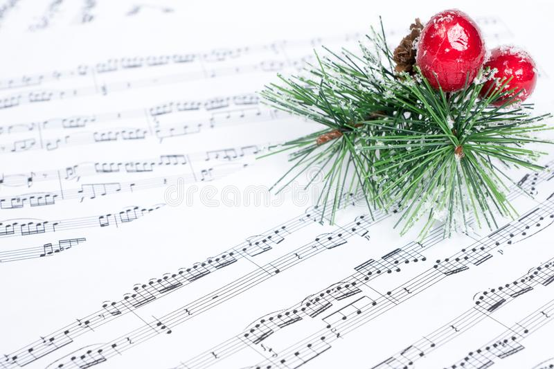 Christmas song, xmas tree branch on music sheet royalty free stock photos
