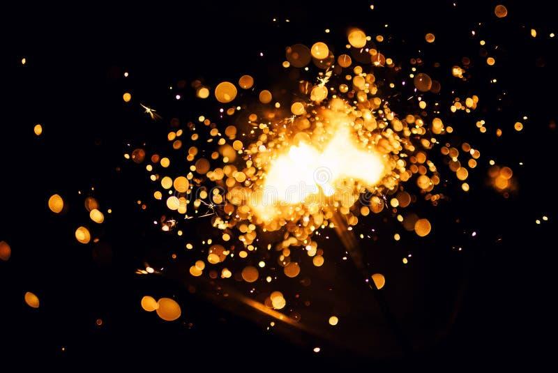 Christmas sparkler. Abstract, background, bengal, black, bright, burn, celebration, closeup, decoration, dust, energy, explosion, festive, fire, firework stock photo