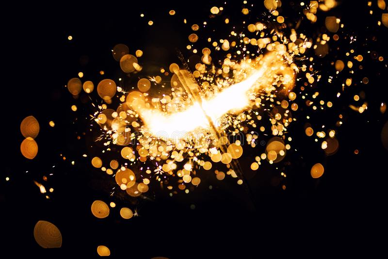 Christmas sparkler. Abstract, background, bengal, black, bright, burn, celebration, closeup, decoration, dust, energy, explosion, festive, fire, firework royalty free stock images