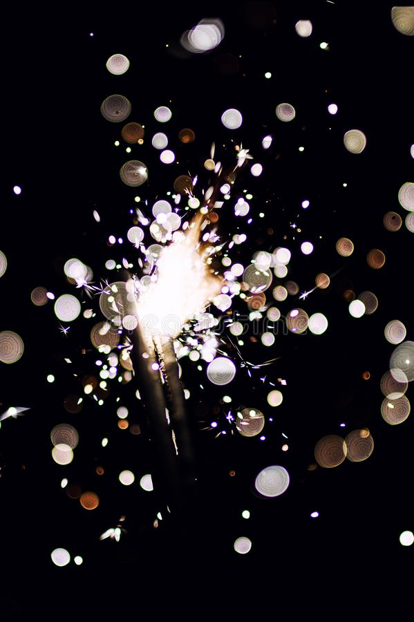 Christmas sparkler. Abstract, background, bengal, black, bright, burn, celebration, closeup, decoration, dust, energy, explosion, festive, fire, firework stock image
