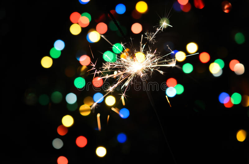 Christmas sparkler. And background of colorful bokeh royalty free stock image