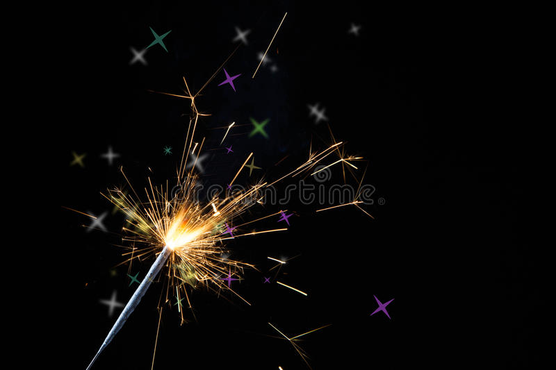 Christmas sparkler. Lighted Christmas sparkler on colorful lights background royalty free stock photos