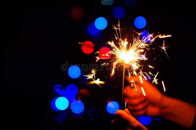 Christmas sparklers. Over dark background with green, red, blue lights, abstract, beauty, bengal, black, bright, burn, celebration, closeup, decoration, dust stock photography