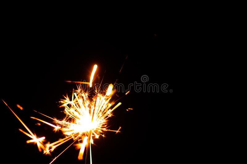 Christmas sparklers. Over dark background, abstract, beauty, bengal, black, bright, burn, celebration, closeup, decoration, dust, energy, explosion, festive royalty free stock photography