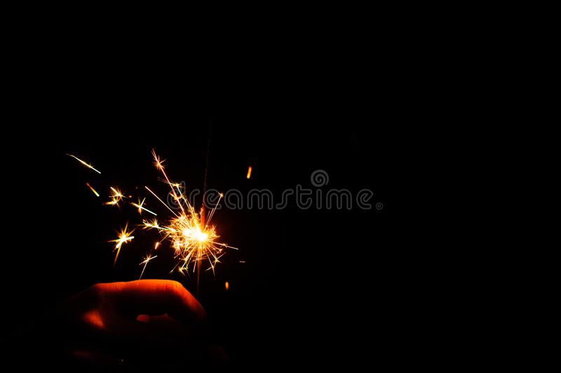 Christmas sparklers. Over dark background, abstract, beauty, bengal, black, bright, burn, celebration, closeup, decoration, dust, energy, explosion, festive stock photography