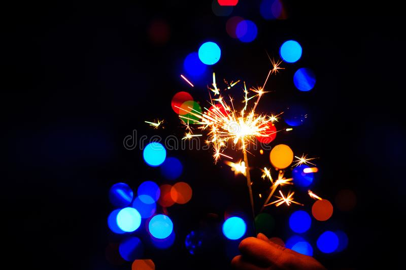 Christmas sparklers. Over dark background with green, red, blue lights, abstract, beauty, bengal, black, bright, burn, celebration, closeup, decoration, dust stock photo