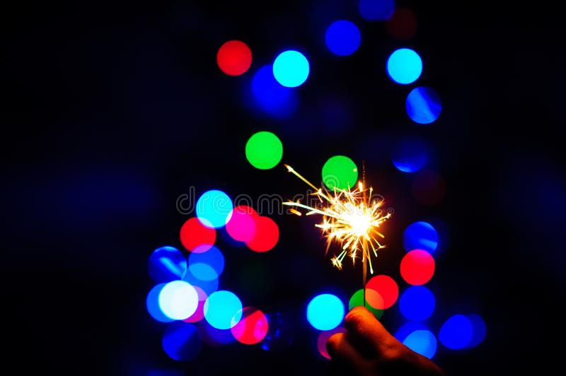 Christmas sparklers. Over dark background with green, red, blue lights, abstract, beauty, bengal, black, bright, burn, celebration, closeup, decoration, dust royalty free stock photo