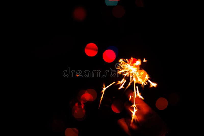 Christmas sparklers. Over dark background with green, red, blue lights, abstract, beauty, bengal, black, bright, burn, celebration, closeup, decoration, dust stock image