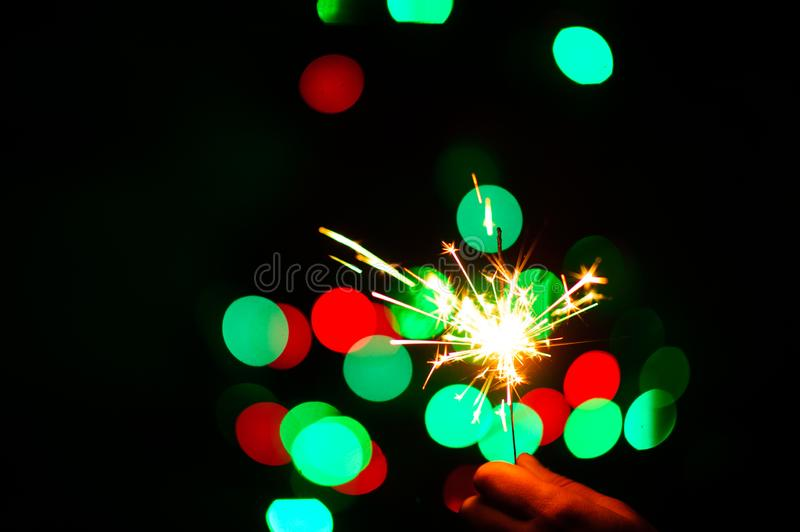 Christmas sparklers. Over dark background with green, red, blue lights, abstract, beauty, bengal, black, bright, burn, celebration, closeup, decoration, dust stock images
