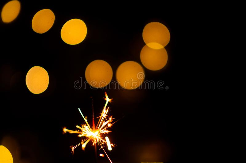 Christmas sparklers. Over dark background with yellow gold lights, abstract, beauty, bengal, black, bright, burn, celebration, closeup, decoration, dust, energy royalty free stock images