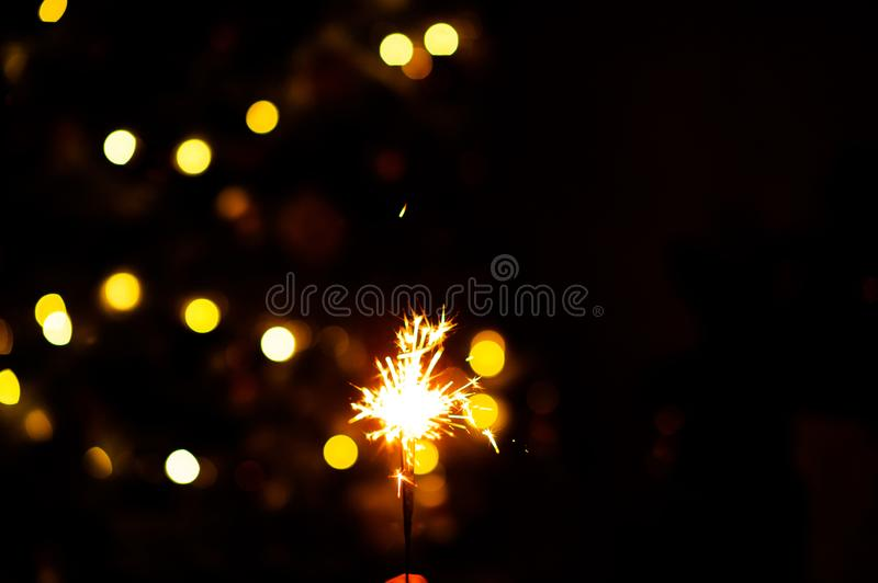 Christmas sparklers. Over dark background with yellow gold lights, abstract, beauty, bengal, black, bright, burn, celebration, closeup, decoration, dust, energy royalty free stock photos