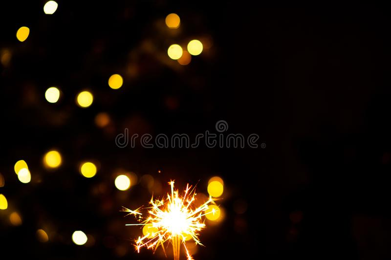 Christmas sparklers. Over dark background with yellow gold lights, abstract, beauty, bengal, black, bright, burn, celebration, closeup, decoration, dust, energy royalty free stock photography