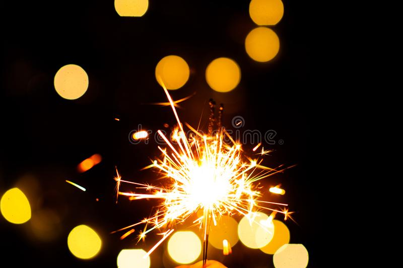 Christmas sparklers. Over dark background with yellow gold lights, abstract, beauty, bengal, black, bright, burn, celebration, closeup, decoration, dust, energy stock image