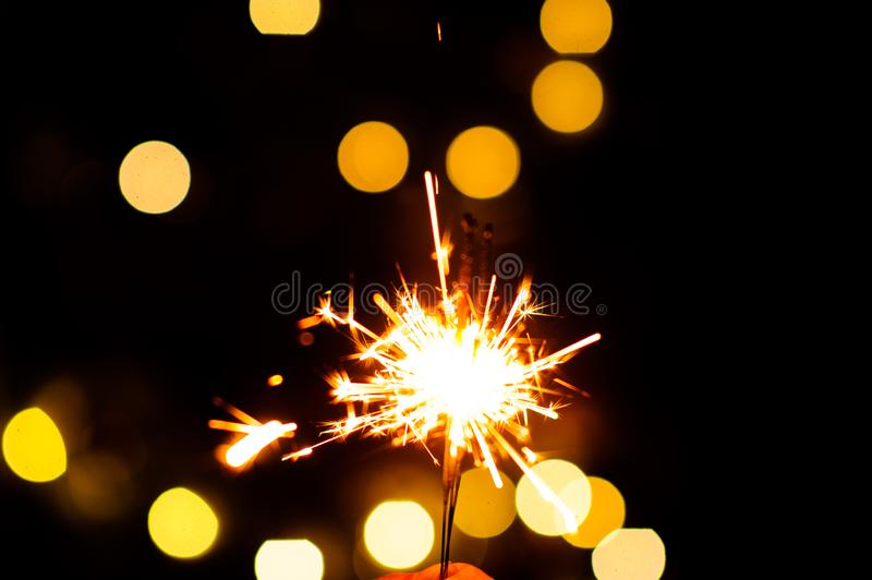 Christmas sparklers. Over dark background with yellow gold lights, abstract, beauty, bengal, black, bright, burn, celebration, closeup, decoration, dust, energy stock photos