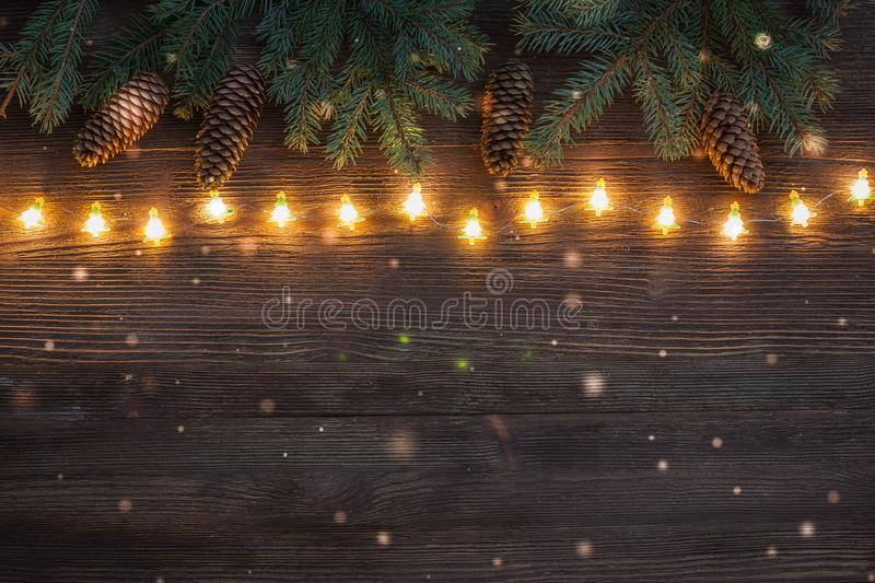 Christmas sparkling Garland with branches of fir tree and cones on the wooden background. Flat lay stock image