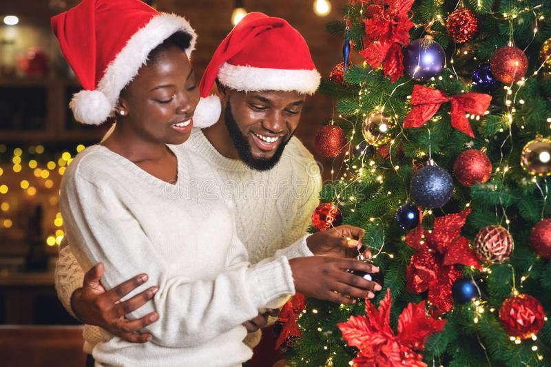 Happy black couple wearing Santa hats and decorating Christmas tree royalty free stock photos