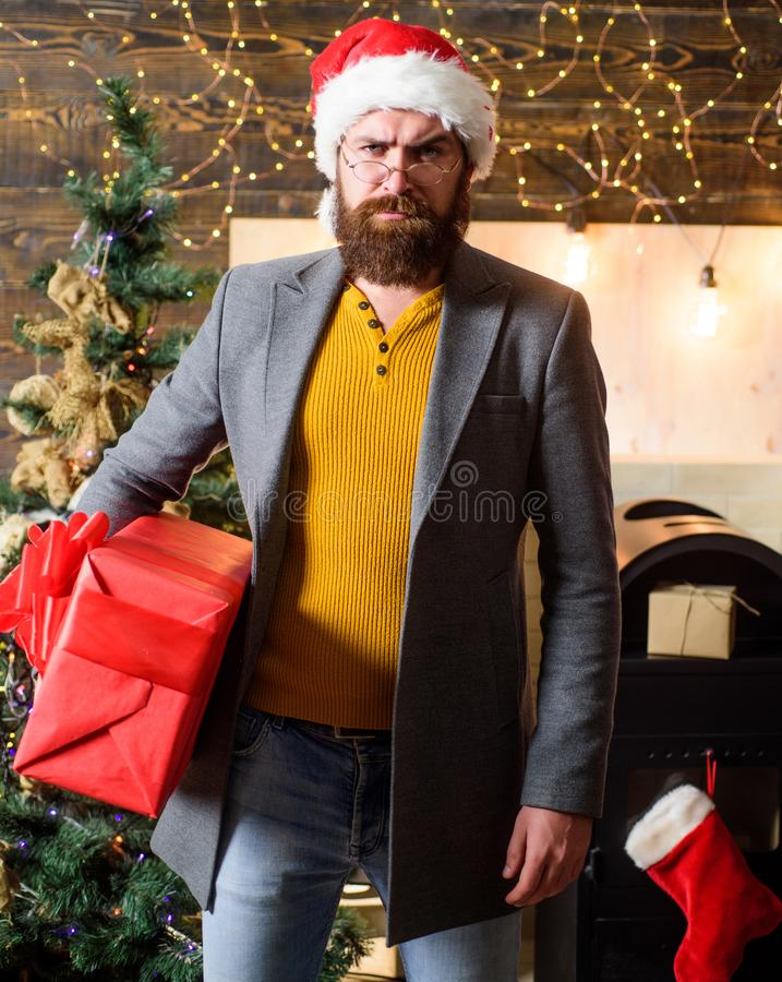 Christmas spirit is here. Spread happiness and joy. Bearded guy wear santa claus hat carry christmas present box. Delivery christmas present. Christmas gift royalty free stock image