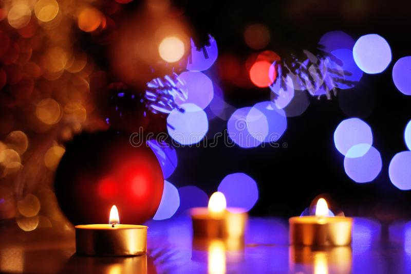 Christmas spirit scene with traditional golden candles and sparkling lights in background royalty free stock photo