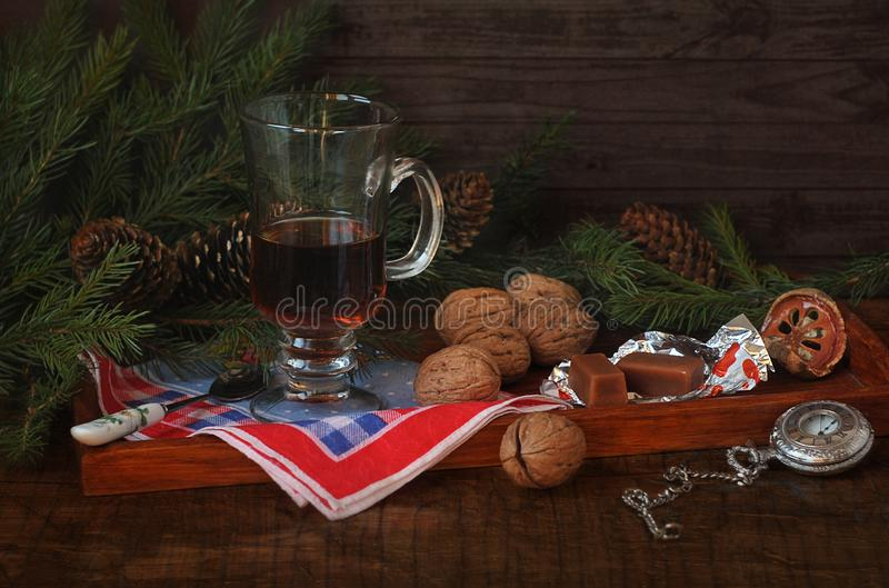 Christmas spruce branches and bumps, coffee, walnuts, candy and antique pocket watch on a dark wooden background. stock photography