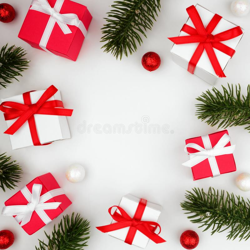 Free Christmas Square Frame Of Red And White Gift Boxes With Branches Over White Royalty Free Stock Photos - 129965108
