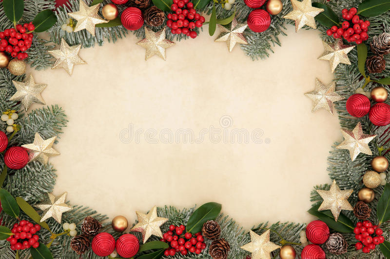 Christmas Star Background Border. Christmas background border with gold star and red bauble decorations, holly, mistletoe, snow covered spruce fir and pine cones royalty free stock images