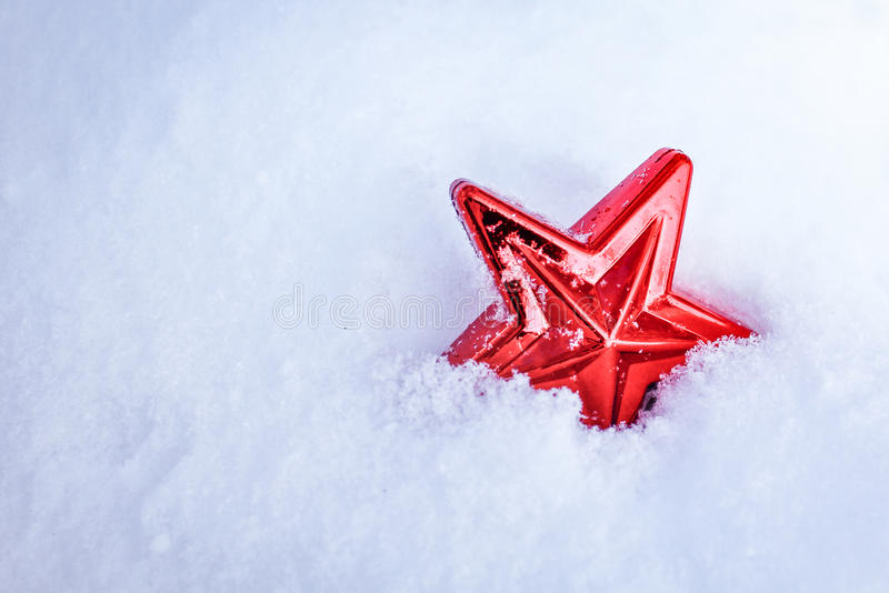 Christmas star. Red christmas star lying in the snow stock photo