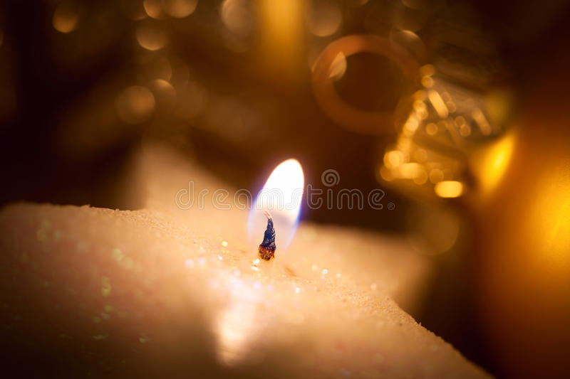 Christmas star-shaped candle with glitter and baubles. Christmas star-shaped burning candle with glitter and baubles - Super Macro shot royalty free stock photo