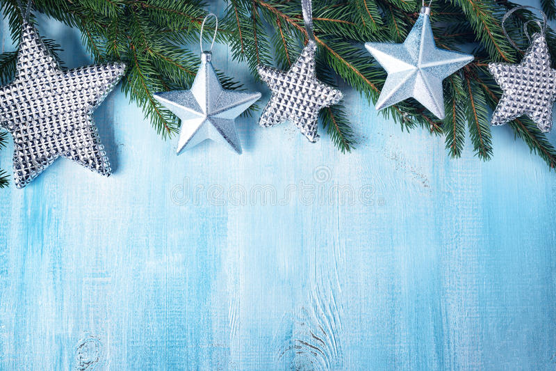 Christmas stars on wooden background with fir tree branches royalty free stock images