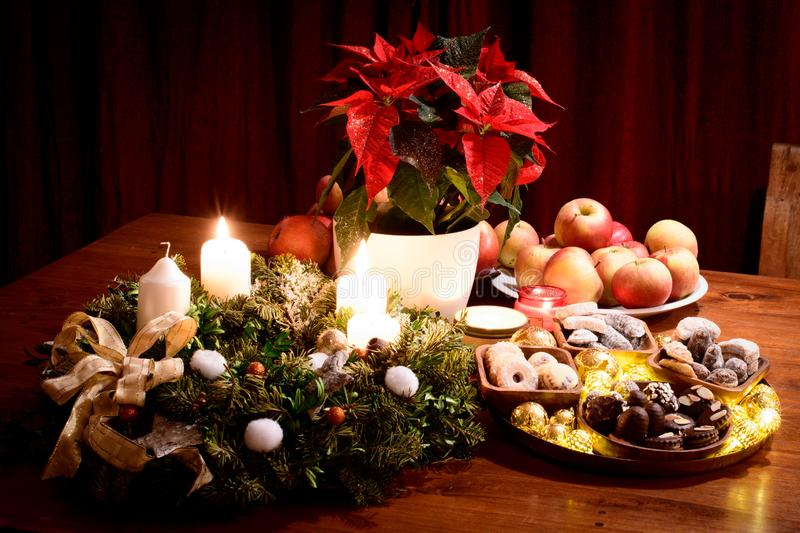 Christmas still life, advent, with Christmass cookies, apples and decorations, two candles lit stock image