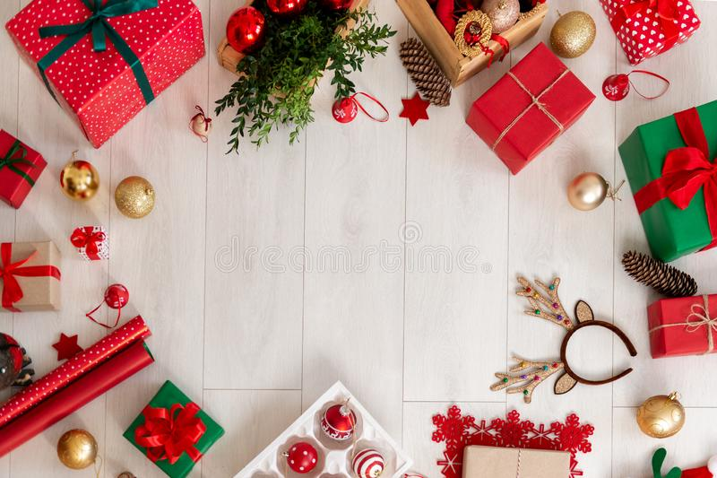 Christmas still life border. Presents, decorations, wrapping paper and ornaments on wooden floor. Top view. Christmas still life border. Presents, decorations royalty free stock photo