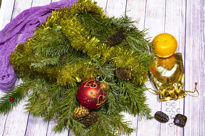 Christmas still life. branches of green spruce with ornaments, a bag of gold, tangerine and candy on a light tree background stock images