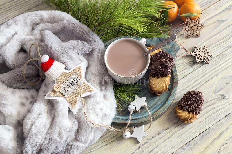 Christmas still life. Cocoa, cookies and scarf on the table close-up. Christmas and New Year still life. Cocoa in a cup, cookies, scarf and Christmas toys on a royalty free stock image