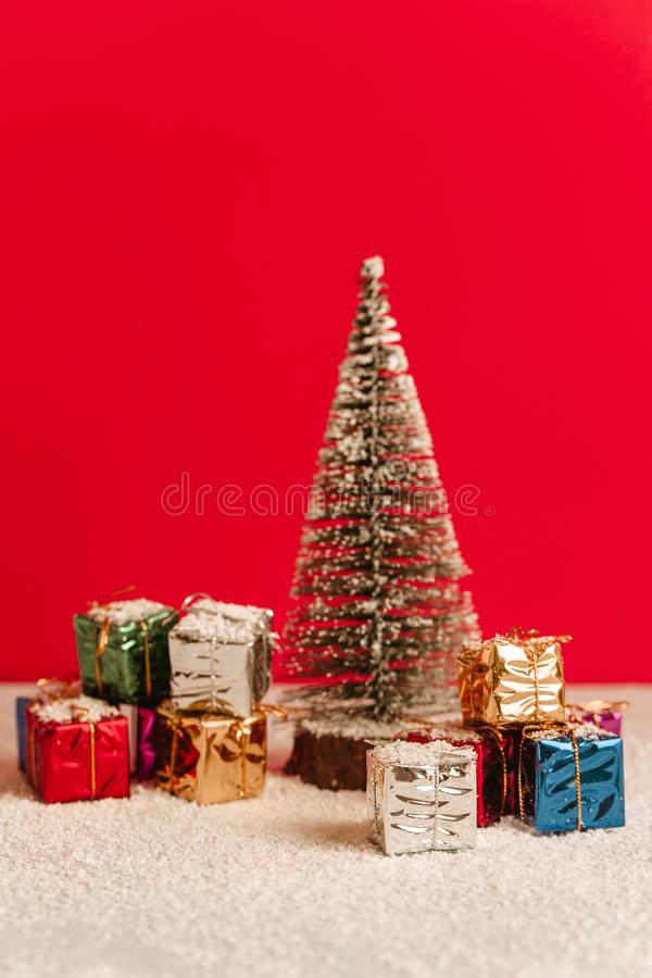 Download Beautiful Christmas Tree Over Snowy Floor With A Bunch Of Gifts Around It Vertical