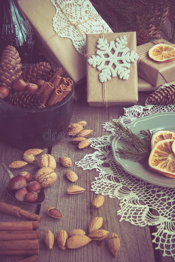 Christmas still life with giftbox, bowl with walnuts, almond, cinnamon, snowflakes on wooden table. Top view. Toned image royalty free stock photos