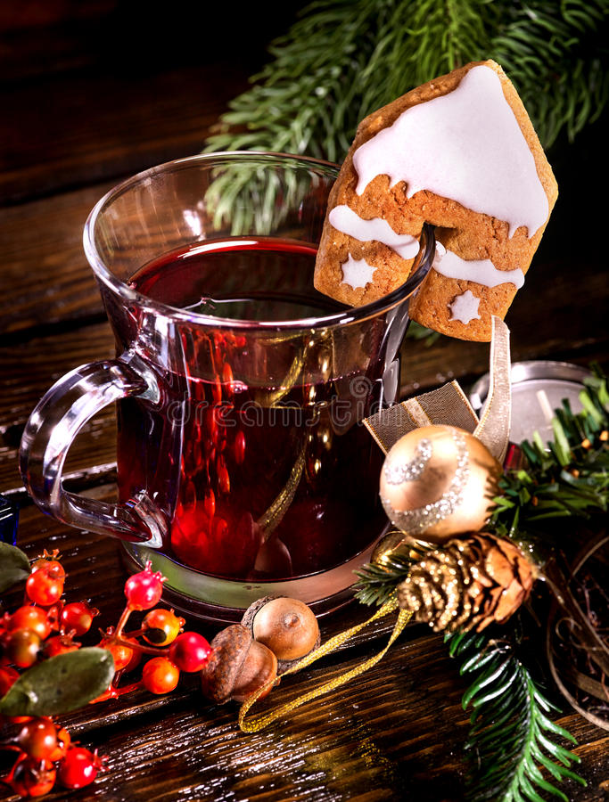 Christmas still life with hot drink and spruce branch. Christmas still life with hot drink. Warming mulled wine with cookie in form of house and Christmas ball stock images