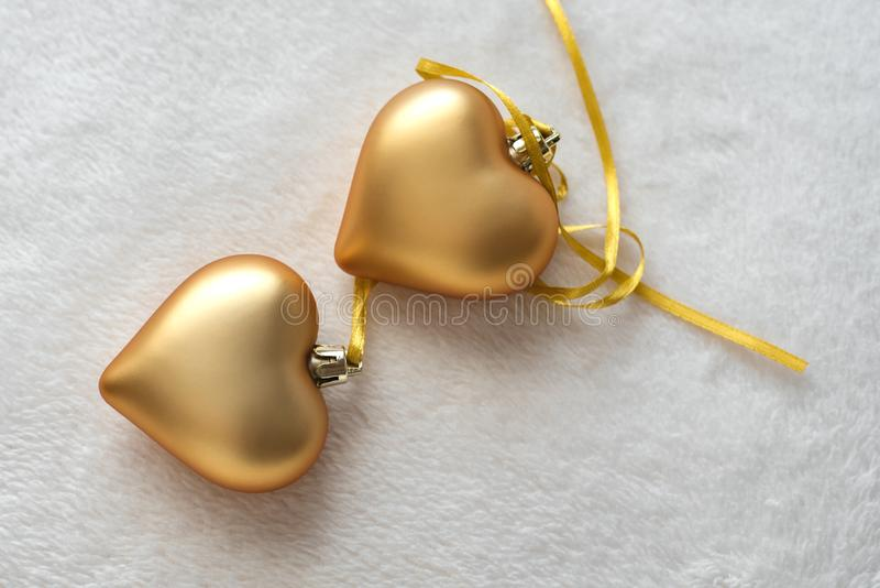 Christmas still life with love for loved ones, two golden hearts on one gold ribbon on a light background. Valentine`s Day Gift stock image