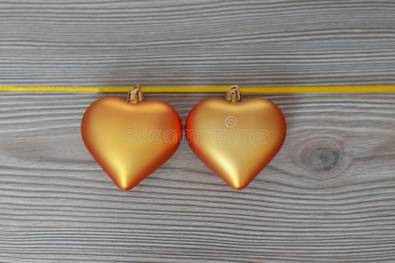 Christmas still life with love for loved ones, two golden hearts on one gold ribbon on a wooden background. Valentine`s Day Gift royalty free stock photo
