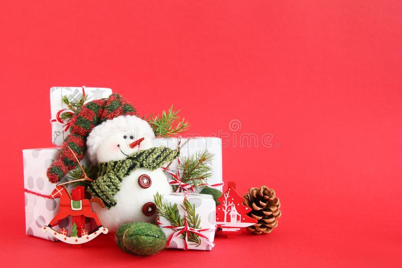 Christmas still life with snowman and gift boxes on a red background, decorated fir branches, pine cone and wooden decorations. stock image