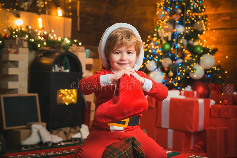 Christmas stocking concept. Child cheerful face got gift in christmas sock. Check contents of christmas stocking. Joy. And happiness. Childhood moments. Kid boy stock photos