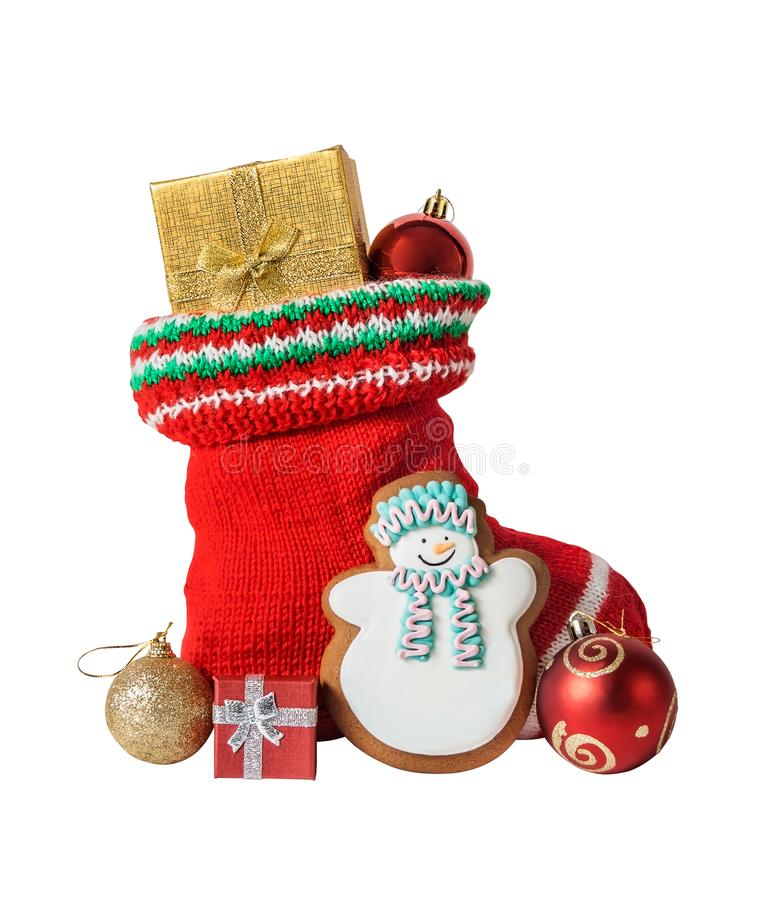 Christmas stocking with gifts, gingerbread cake and balls isolated stock photography