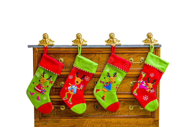 Christmas Stockings. Four colorful Christmas stockings hanging from brass figurine holders on top of an antique chest royalty free stock images