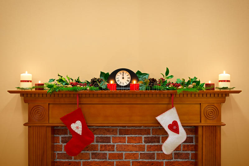 Christmas stockings and garland on a mantlepiece stock images